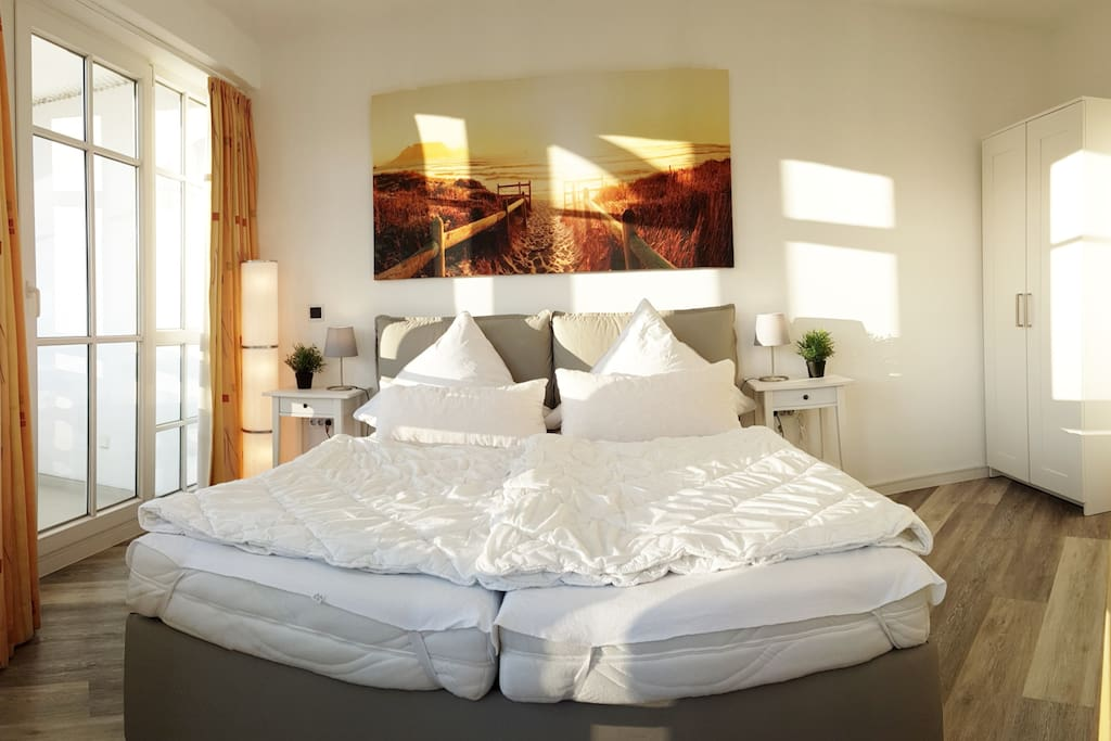 Das freundliche Schlafzimmer mit bodentiefen Fenstern lässt nach dem Aufziehen der Vorhänge direkt die ersten Sonnenstrahlen des Tages hinein. Das Schlafzimmer hat einen separaten eigenen Balkon.