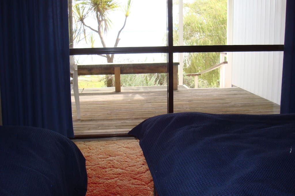 Two single beds looking out to deck and lake.