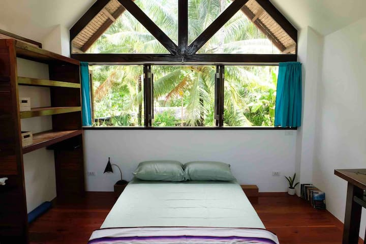 The gallery-style loft bedroom, with large windows, high ceiling, ceiling fan, queen size bed with luxury spring mattress, open wardrobe, and desk.