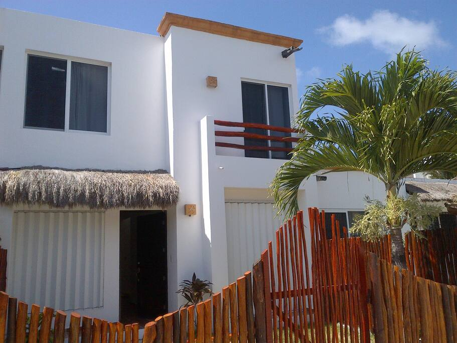 Front of the house with garden and 2 double bedrooms and studio/bedroom with sun shutters to keep the house fresh .