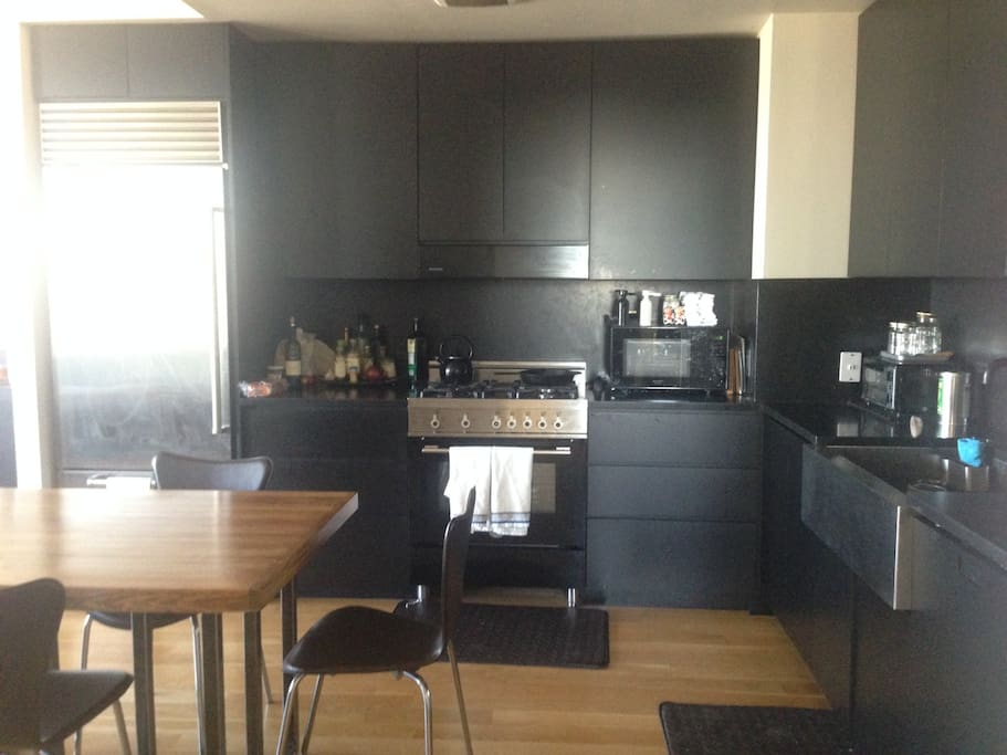 Kitchen with gas range, fridge with ice maker, microwave, toaster oven, dishwasher, coffee maker, french press and large farm sink.