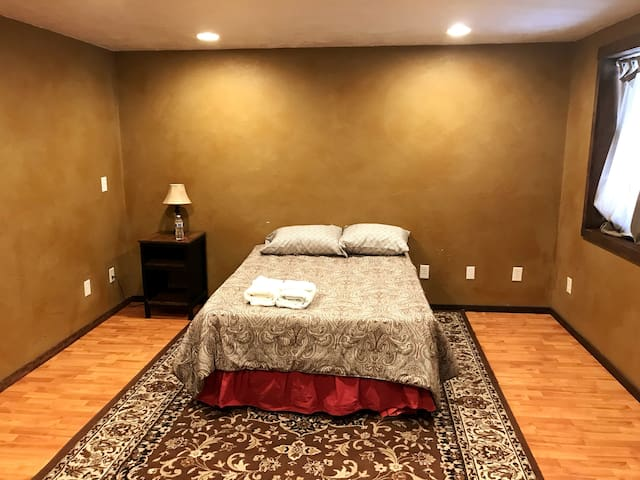 """Bedroom number 6 - """"The Music Room."""" 20'x20'. A queen blow up mattress Is additionally available in the closet of this room should you need to put a second bed in here. You will also find an electric guitar, and microphone and amp for karaoke."""