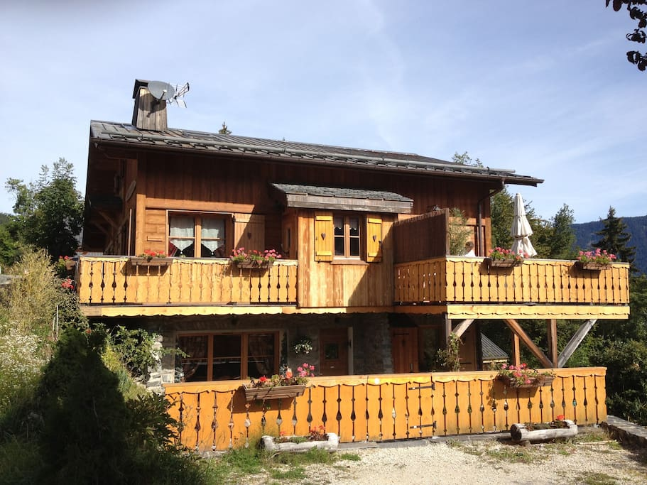 Chalet in the summer months. Balcony with dining furniture and sun umbrella & deckchairs.