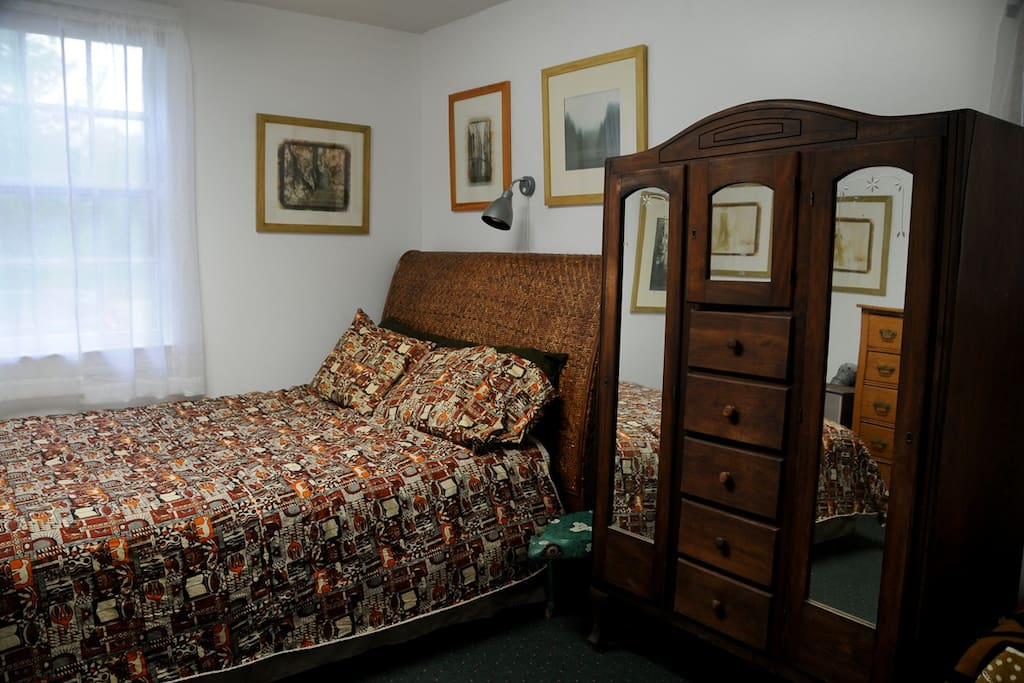 The room has a queen bed and wardrobe. Inside the wardrobe are courtesy robes and slippers, an iron and hair dryer.