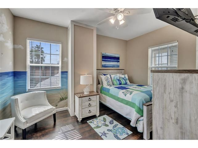 Bedroom on the second floor with comfortable full bed, Smart TV, and ceiling fan.