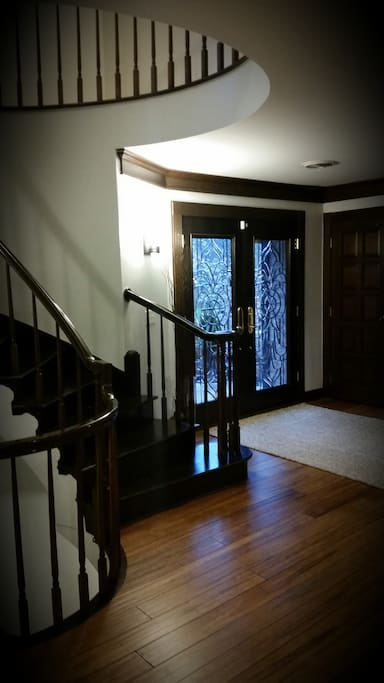 Double front doors leads to an open foyer with elegant spiral staircase