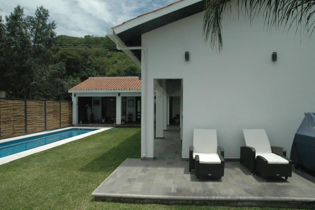 Vista general del concepto: alberca, sala, jardín, pasillo acceso a habitaciones, terraza, asador.