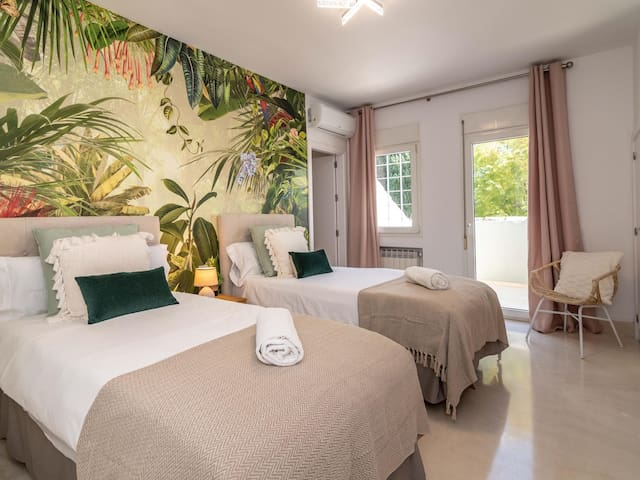 Bedroom # 2 (Upper floor) – Two single beds (90 x 200 cm), air conditioning, private terrace, and en-suite bathroom featuring a bathtub-shower and single vanity.