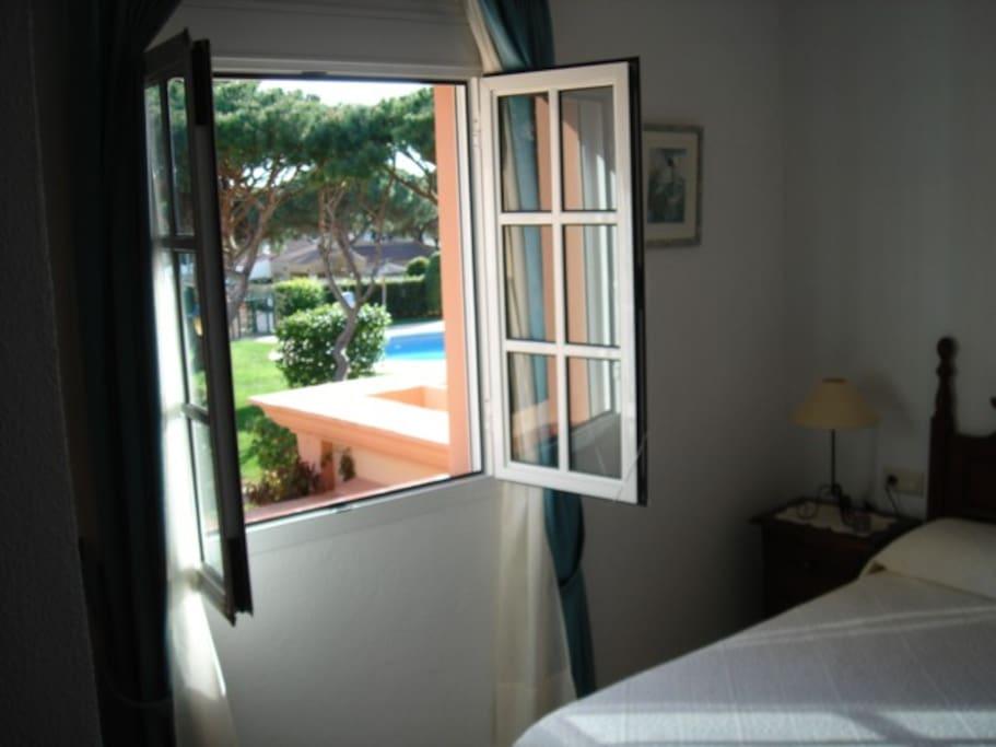 Vista de la piscina desde el dormitorio Principal (con TV y armario empotrado).