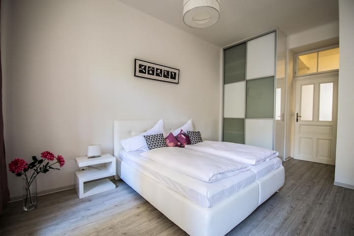 Bright cozy bedroom with a double bed and a wardrobe.