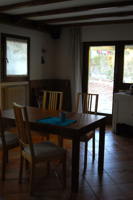 Table in the living room, with a view on the garden. Tavolo del salotto con vista sul giardino.