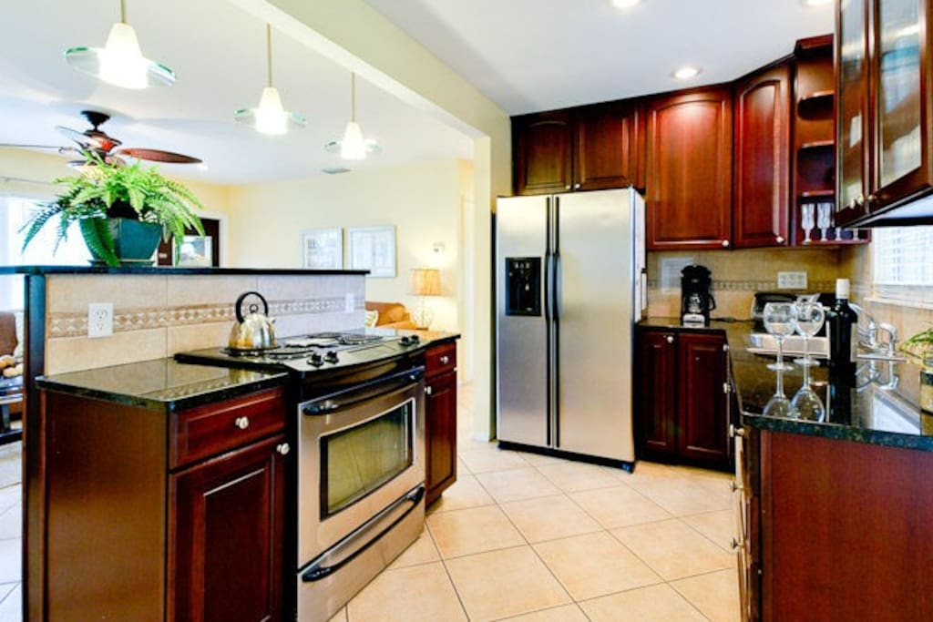 Gourmet kitchen with granite counters and new stainless steel appliances make cooking in your vacation home a delight or pick up easy take out & chill out around private pool!