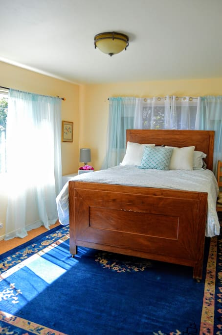 The lovely, airy and bright master suite. The room boasts a queen-sized, extremely comfortable mattress. Pull down curtains make it easy to have as much light/privacy in the room as desired.