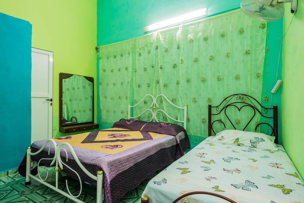 Primera habitación con capacidad para 3 personas, una cama matrimonial grande y una individual, climatizada y con ventiladores, tocador para guardar pertenencias, maquillaje etc., perchas para ropa y baño privado.