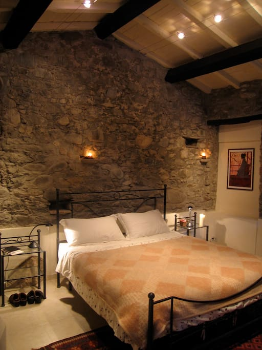 The bedroom with stone walls and cathedral ceiling; very romantic by candlelight