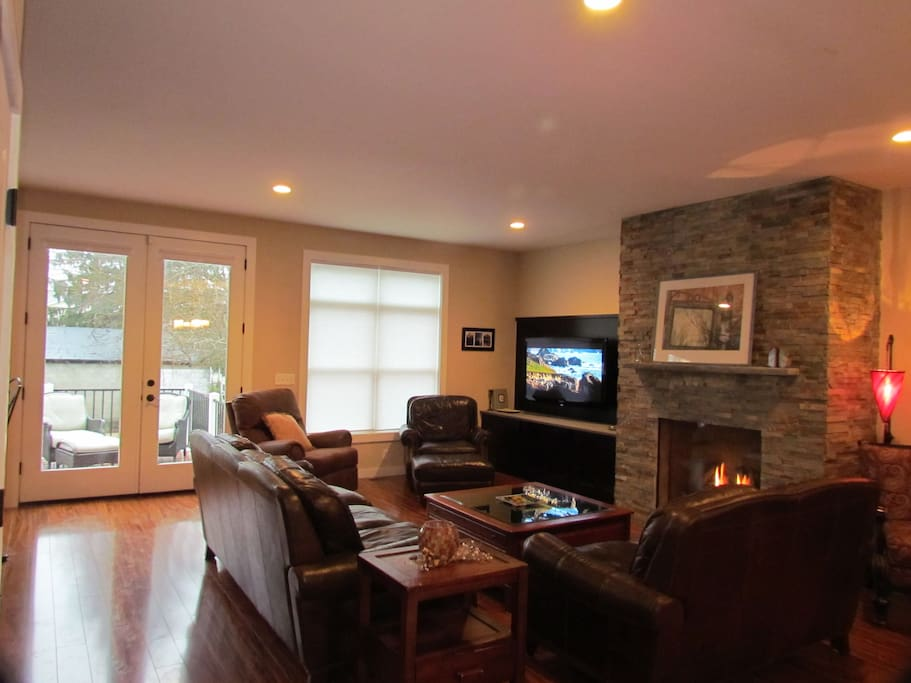 Family room w/ leather furniture ,hardwood floors , fireplace and deck .