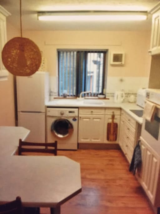 Kitchen area with washing machine , fridge freezer , microwave , hot plate Kettle and Toaster Breakfast bar