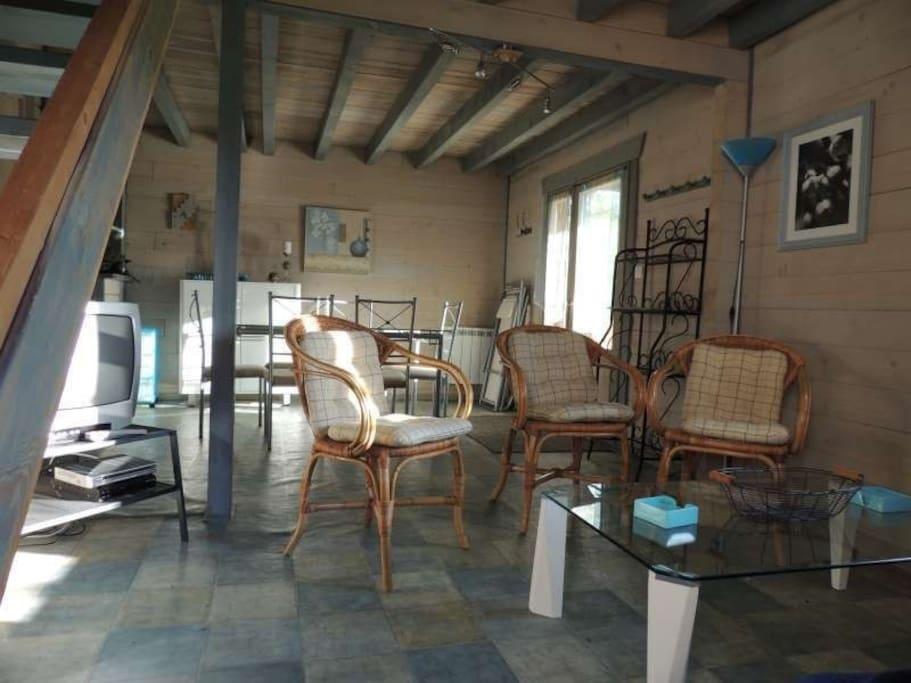 Pièce de vie (téléviseur remplacé par écran plat) partie cuisine sur la gauche. Terrasse couverte.