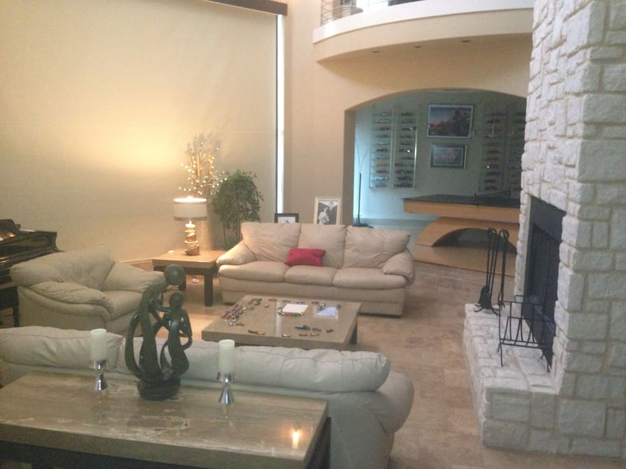 Electric shades for privacy, wood-burning fireplace.  Room flanked by game room and bar