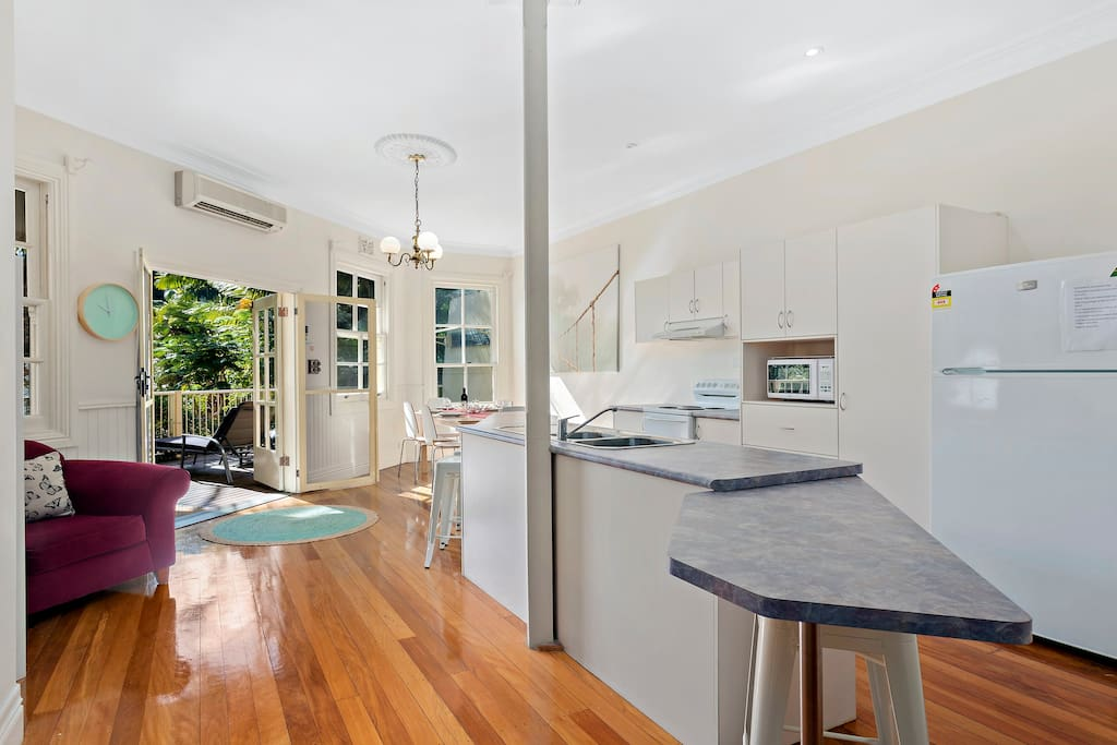 Beautiful kitchen/dining area.  The french doors lead out to the large sun filled balcony overlooking tropical gardens.