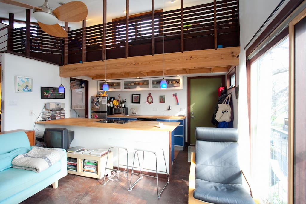 View of kitchen and sleeping/study loft from living area.
