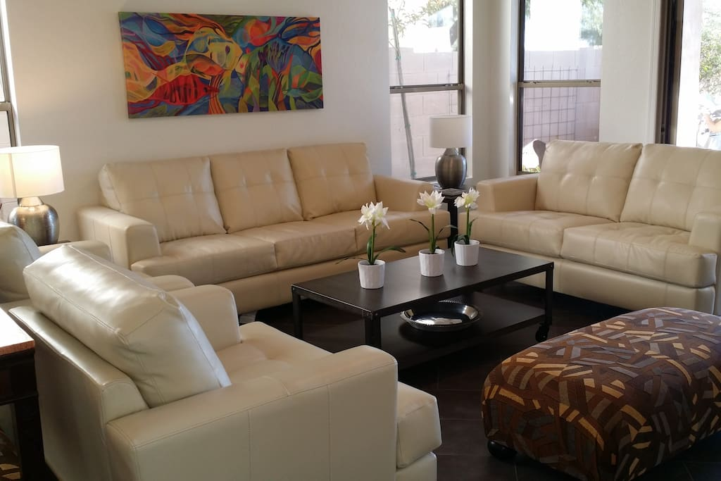 Leather couches and  two large ottomans provide seating for 7 in front of large TV.