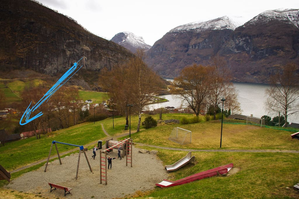 The arrow points at the house where the apartment is. It lies near a playground, as vell as the senter and the fjord.