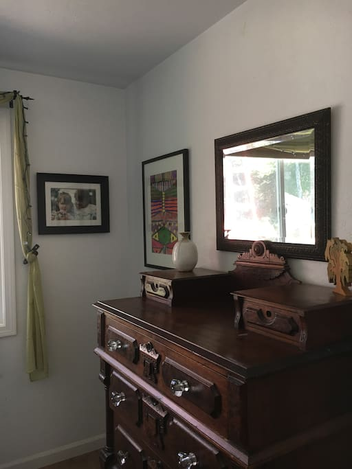 Antique dresser matches the age and style of the bed frame.