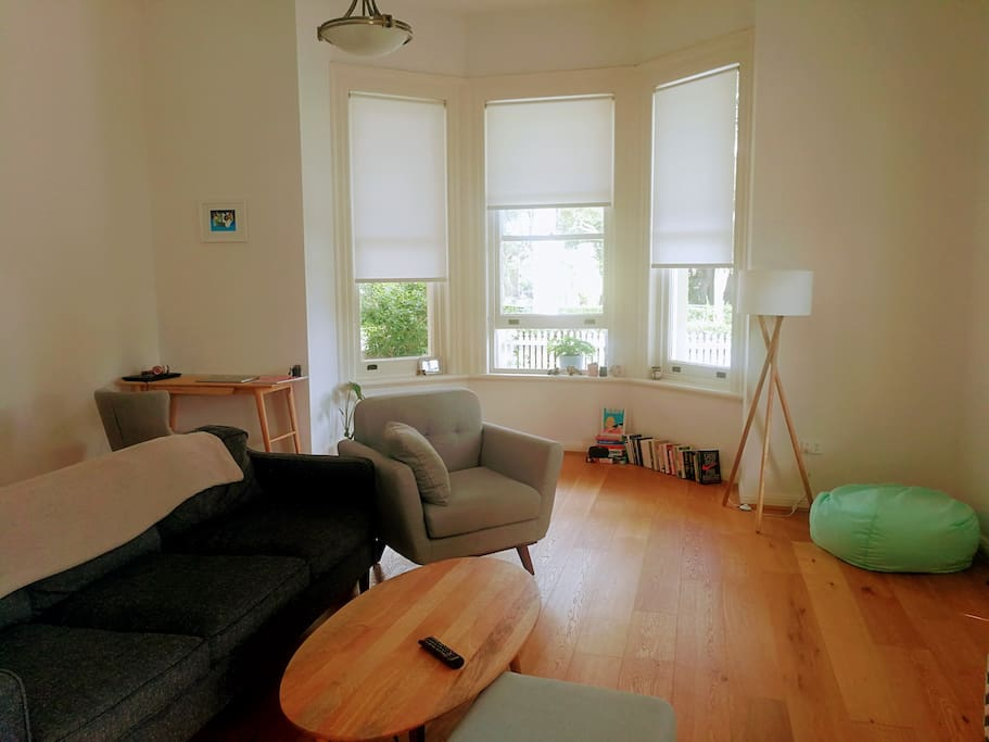 Bright, open-plan living room with beautiful bay window. Newly furnished, uncluttered with hardwood floors and two side doors which open on to your personal wrap around veranda.