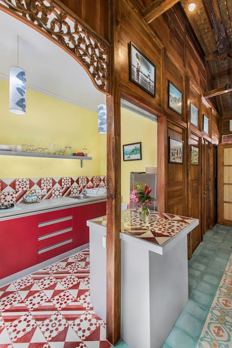 A fully equipped modern kitchen in bright colors (handcrafted cement tiles), big refrigerator, a bar table between kitchen and living room