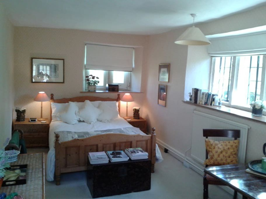 The bedroom has three windows and overlooks the back garden and courtyard