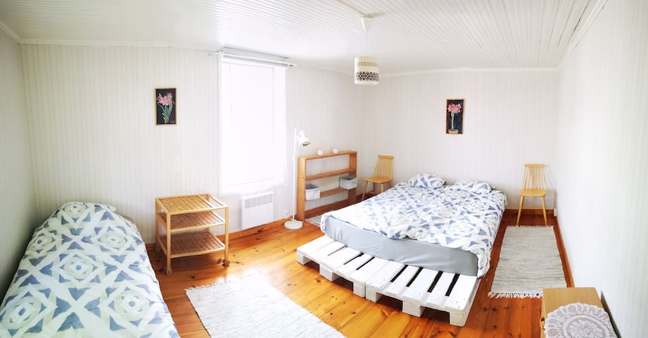 Bedroom with one double bed and one single bed and view to the sea