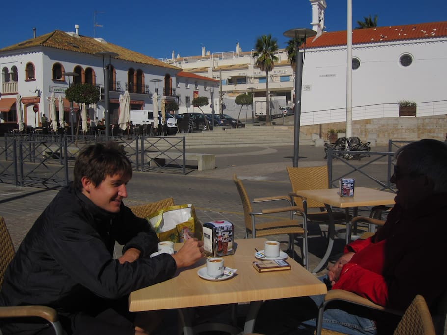Relax with a coffee in village  square , on beachfront .