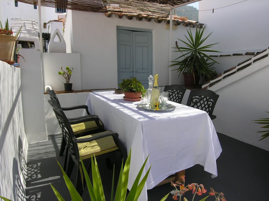 Spacious roof terrace with dining table and relaxing sunbeds, partly shaded.