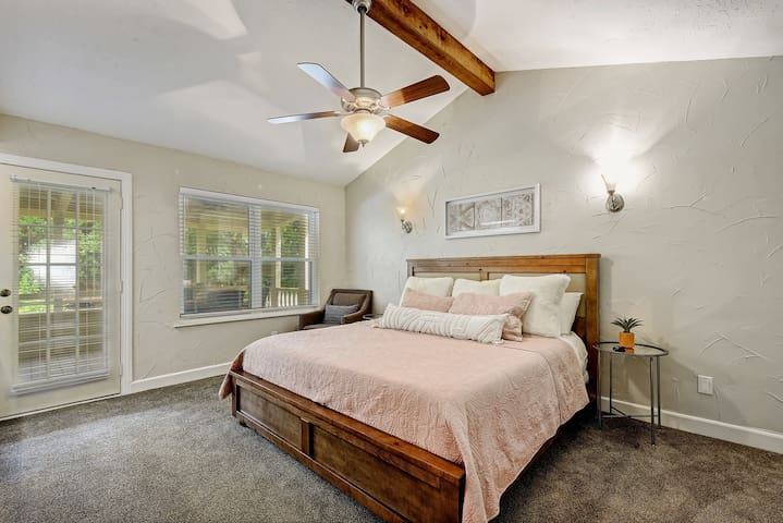 Probably the coziest feeling bedroom, offering a king size wooden bed, accent chair, and vanity with sink, make-up mirror, and stool.