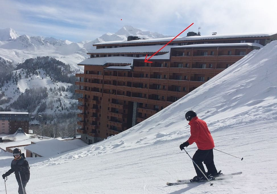 View of the building from the ski hill - apartment indicated with red arrow