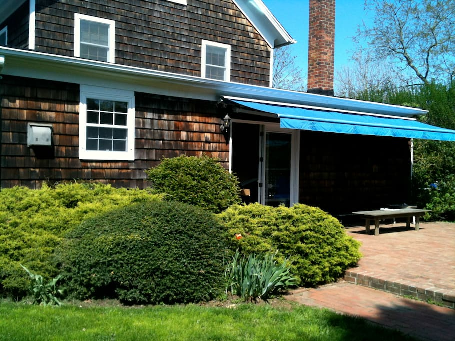 Brick terrace with awning for shade.