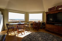 Inside guest house, looking south, living room/dining room are combined for a large family area.  Panoramic view of Martha's Vineyard in 3 picture windows.