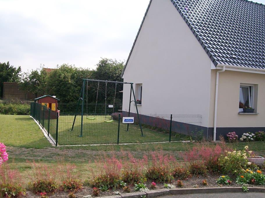 Jardin clôturé avec balançoire et cabane du trappeur