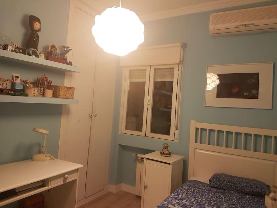 habitación individual con tv, armario, y escritorio