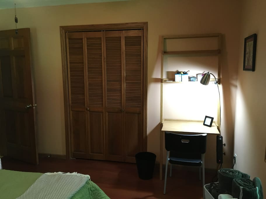 Desk and large closet with hangers.