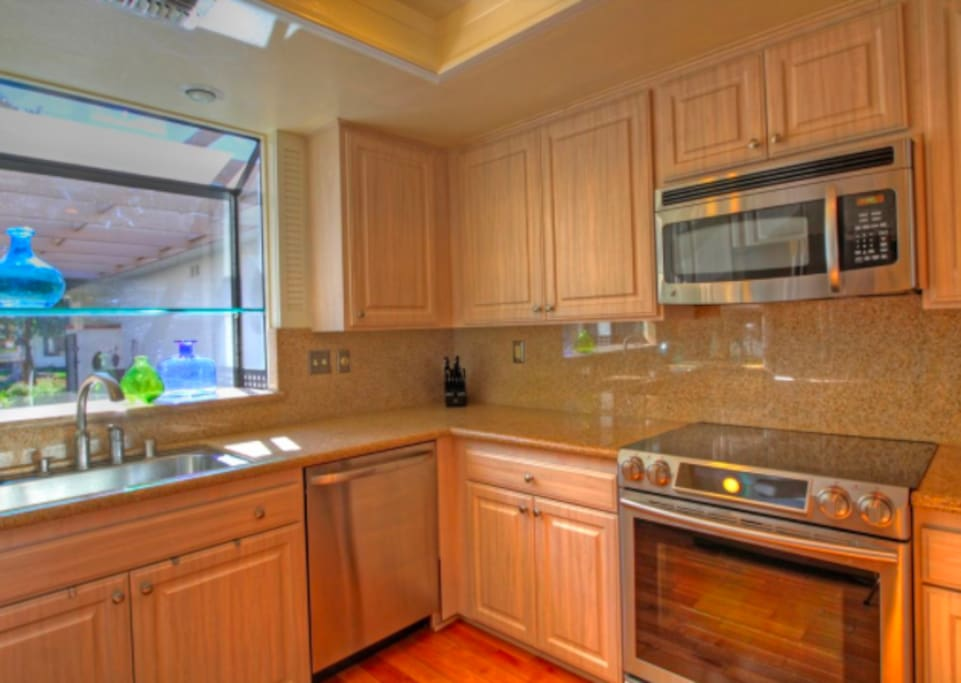 Kitchen with slab granite counters. stainless appliances