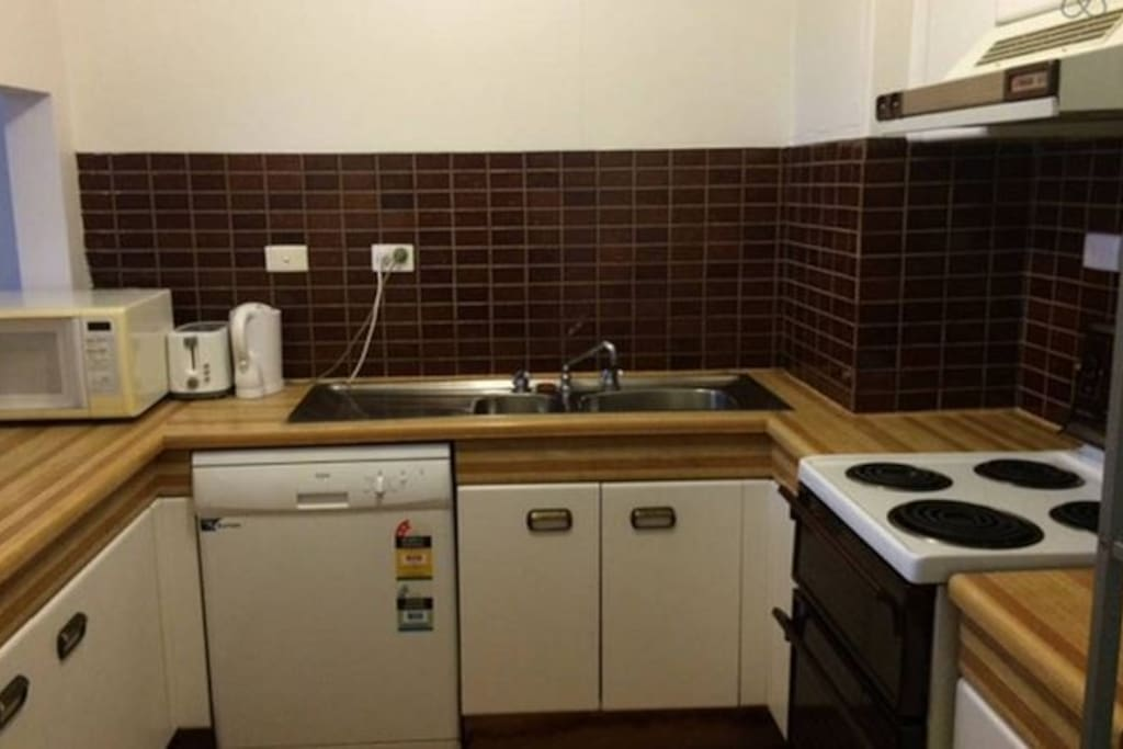 full kitchen with oven dishwasher and cooking utensils