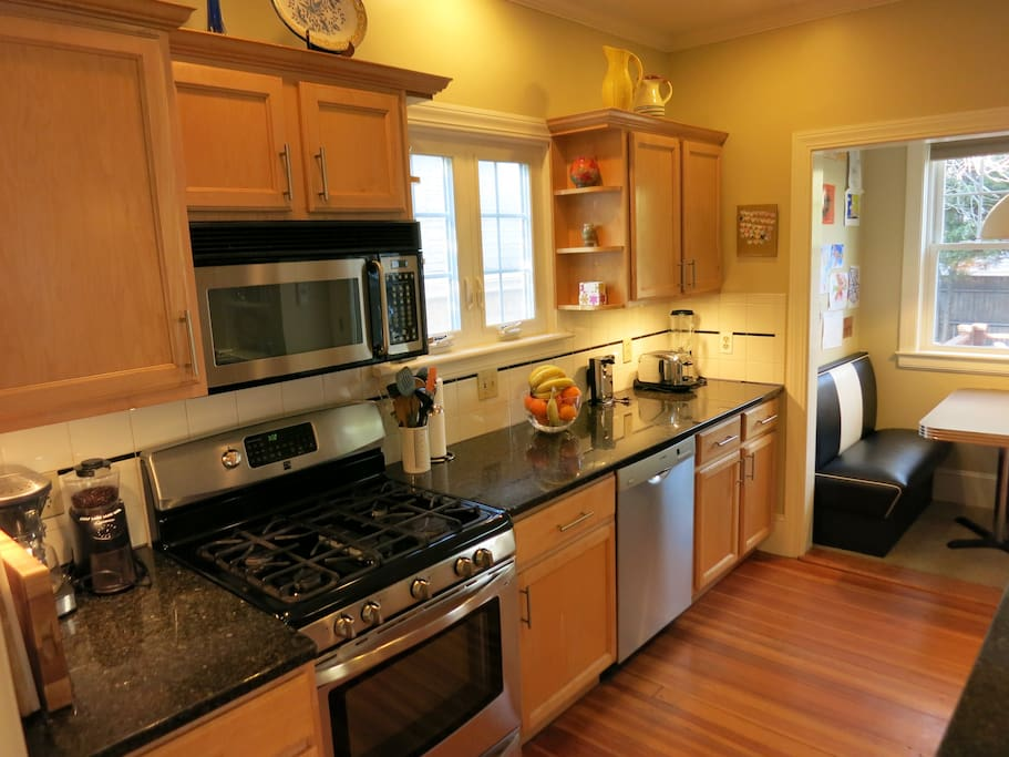 Modern kitchen with convection gas oven, dishwasher and built-in retro dining booth.