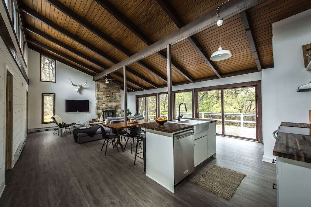 One large open space with 15 ft ceilings, natural stone wood burning fireplace, and views of nature from every direction