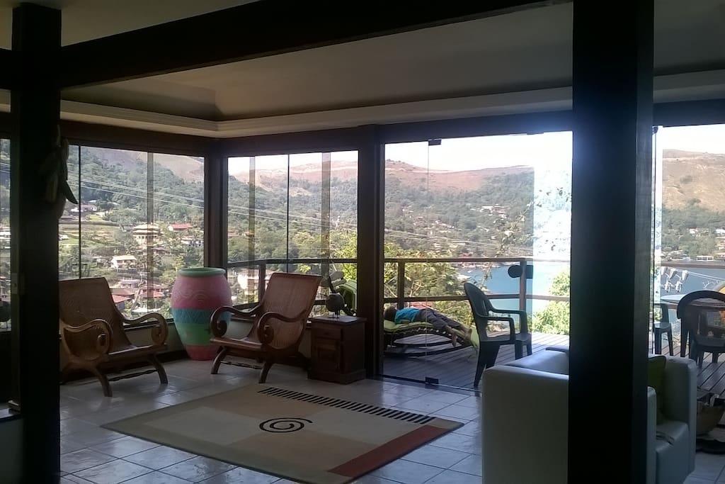 Sala de estar envidraçada com vista para Ilha Grande e montanhas