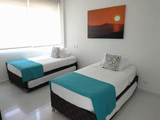 Segunda habitación con cuatro camas sencillas, closet y baño
