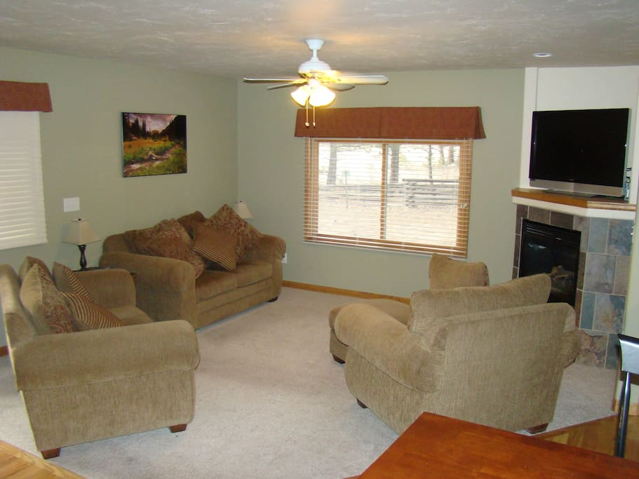 Spacious living room with flatscreen satellite TV and fireplace.