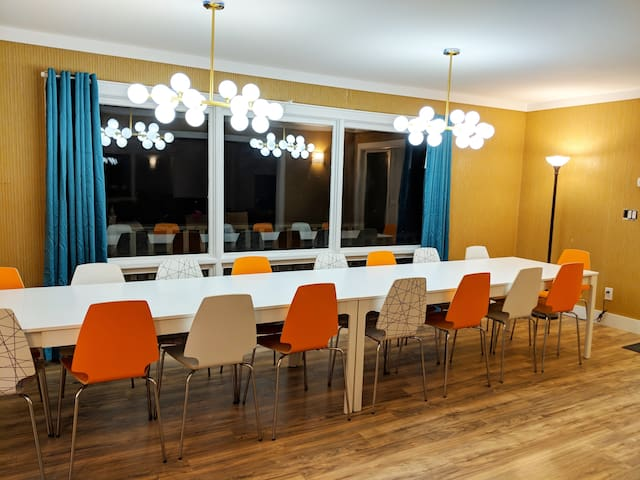 Dining room seats 18. The orange twill wallpaper is original from 1965.
