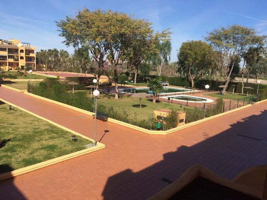 Amplias zonas verdes, piscina y pista de tennis.